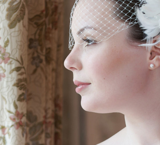 Pretty bride looking out of window and smiling on her wedding day